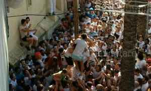 Residents in Spain battle to climb a pole during the infamous La Tomatina festival