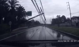 Terrifying moment electricity pylons are blown onto car during Thai storm