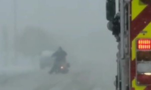 Firetruck Escorts Motorcycle Through the Snow
