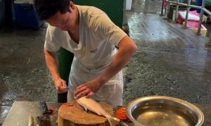 Man Prepares Milkfish in Philippine Market