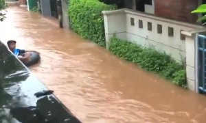 Kid floats down tube in flooded streets of Jakarta