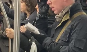 Person Climbs into Handlebars on Subway Train