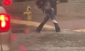 Boy Carries Fellow Students Across Flooded Street