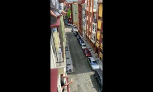 Man in Italy pours a drink for his neighbor two floors below