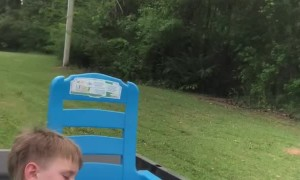 Tuckered Toddler Nods Off during Lawnmower Ride
