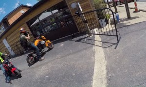 Rider Wheelies into Metal Fencing by Restaurant