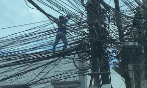 Worker Climbs Along Electric Wires