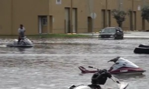 People ride jet skis through flooded Miami streets