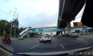 Vehicle Swerves into Car and Forces it onto Barricade