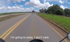 Motorcyclist Passes Underneath Large Vehicle on the Road