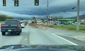 Logging truck spills load all over highway, causes massive damage