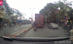 Scooter Tries to Squeeze Past Truck