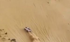 Full throttle truck drives up insanely steep sand dune
