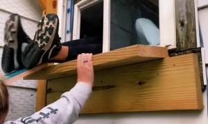 Girl Fits Inside Small Cat Door Cut into a Window