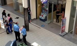 Man Casually Strolls Past Woman Pointing Gun Inside Mall
