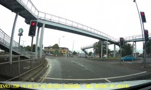 Oncoming Car Tipped to Two Wheels in Traffic
