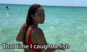 Woman in the ocean catches fish with her bare hands
