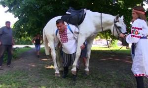 Strong Man Walks Carrying a Horse