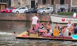 Guy Pushes Raft of People Down Canal