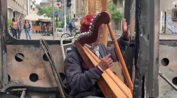 Musician Performs in Burned Out Bus