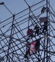 Indian men scale a billboard scaffold in political protest
